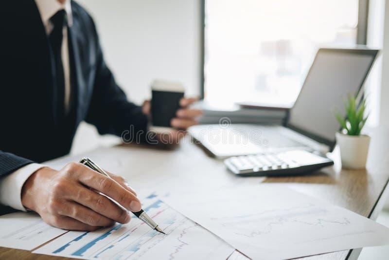 Homem de negócios que trabalha o projeto novo no laptop com documento do relatório e para analisar, calculando dados financeiros  fotografia de stock royalty free