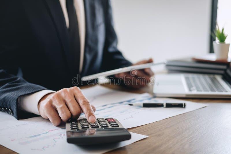 Homem de negócios que trabalha o projeto novo no laptop com documento do relatório e para analisar, calculando dados financeiros  imagens de stock