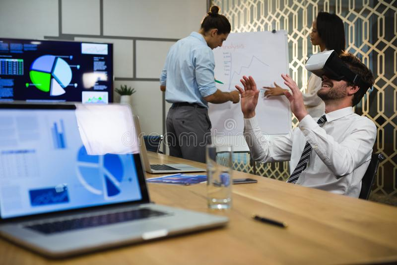 Homem de negócios que usa auriculares da realidade virtual quando colegas que discutem sobre a carta de aleta imagens de stock