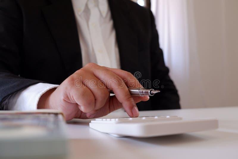 Homem de negócios que usa a calculadora com dinheiro na mesa imagens de stock