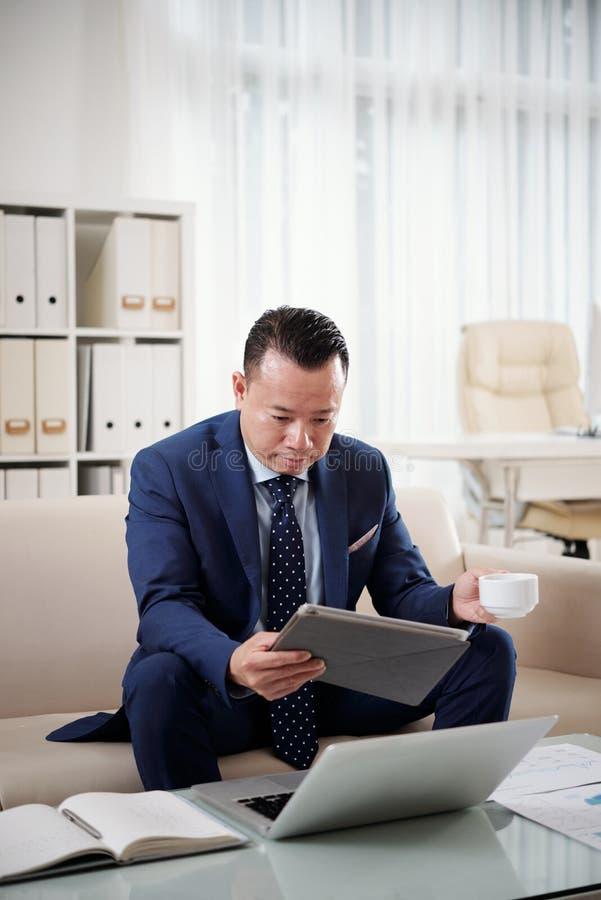 Homem de negócios que usa dispositivos modernos em seu trabalho foto de stock royalty free