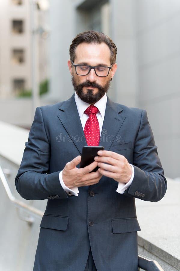 Homem de negócios que usa a leitura do app do telefone celular fora do escritório na cidade com construções dos arranha-céus no f imagens de stock