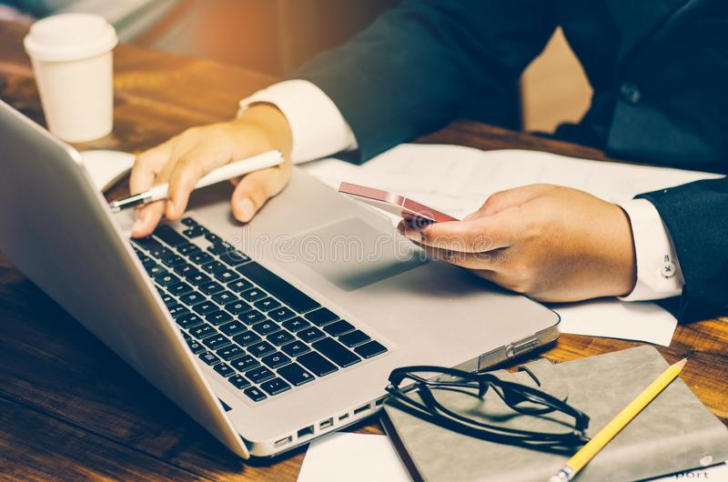 Homem de negócios que usa o cartão de crédito com um portátil para comprar na linha imagem de stock royalty free