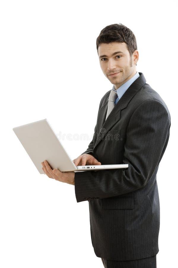 Homem de negócios que usa o computador portátil fotografia de stock