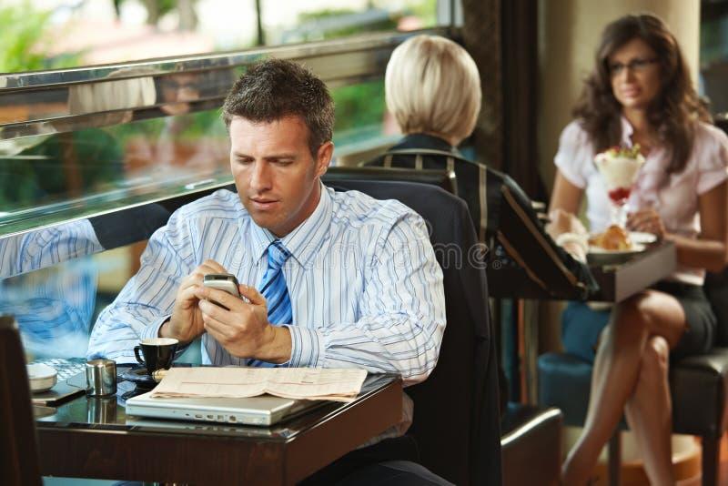 Homem de negócios que usa o móbil no café imagens de stock royalty free