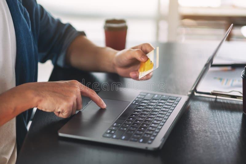 Homem de negócios que usa o portátil e o cartão de crédito para comprar foto de stock royalty free
