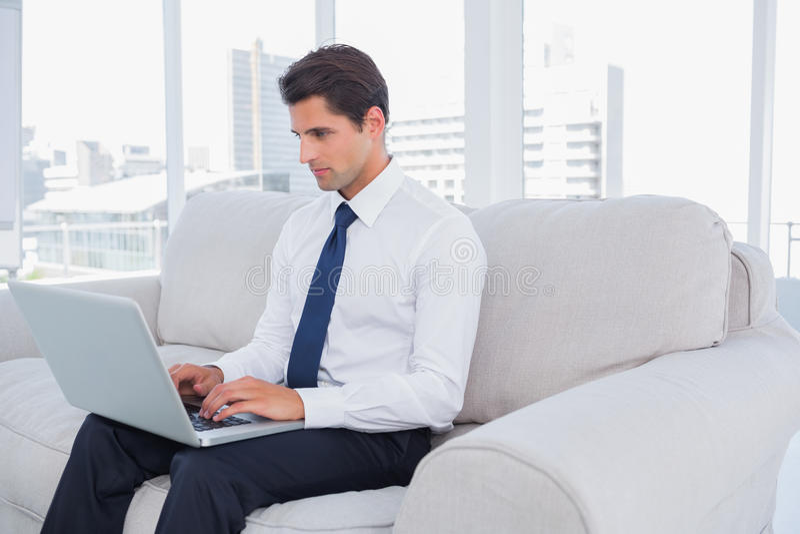Homem de negócios que usa o portátil em um sofá foto de stock royalty free
