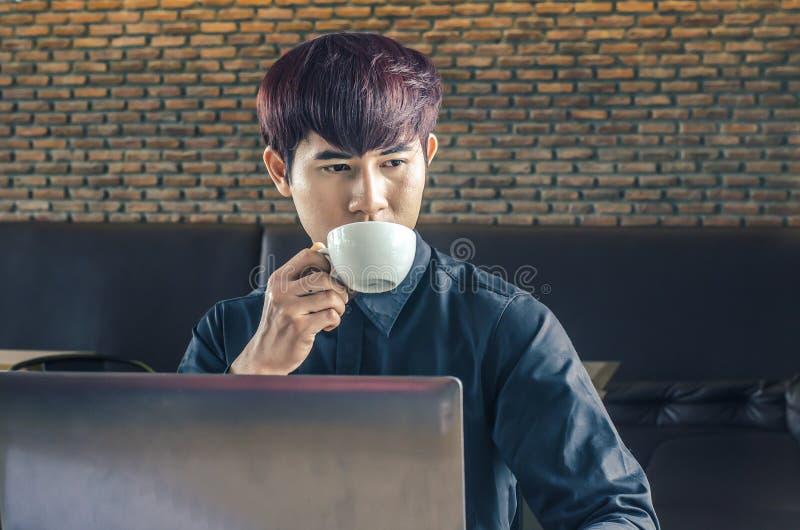 Homem de negócios que usa o portátil na tabela de madeira com uma xícara de café fotos de stock royalty free