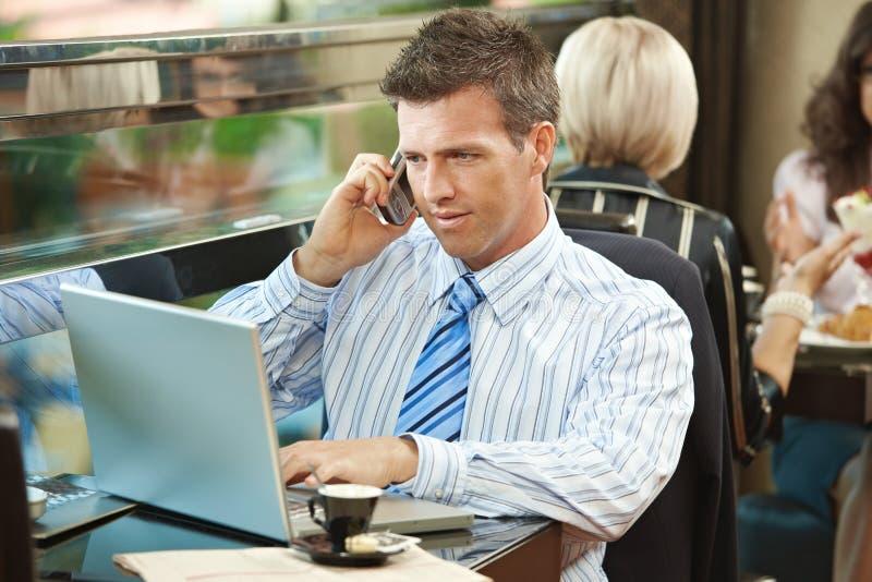 Homem de negócios que usa o portátil no café fotos de stock royalty free