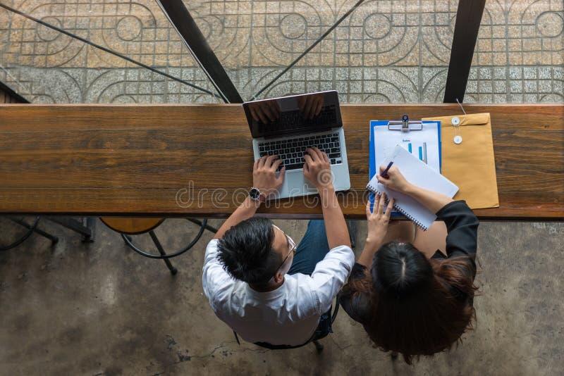 Homem de negócios que usa o portátil, notas da escrita da mulher de negócios foto de stock