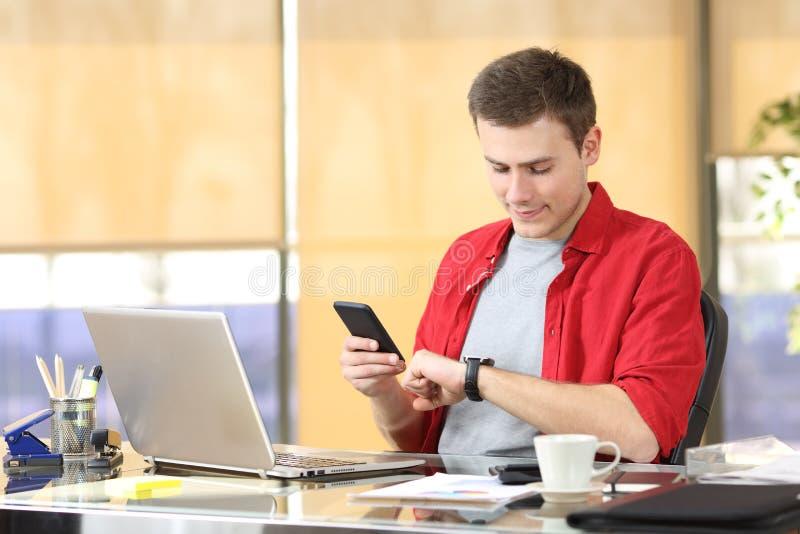 Homem de negócios que usa o relógio e o telefone celular espertos imagem de stock