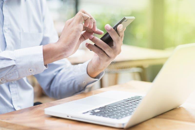 Homem de negócios que usa o smartphone e o laptop fotos de stock