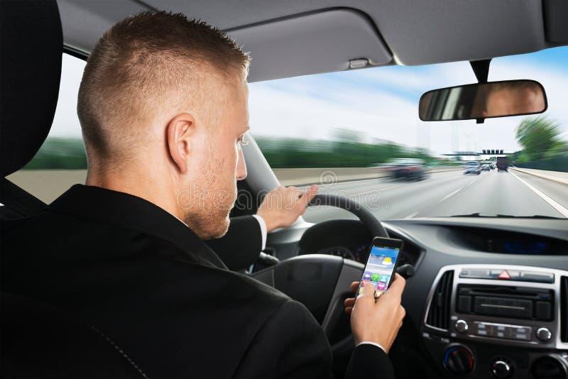 Homem de negócios que usa o telefone celular ao conduzir um carro imagem de stock