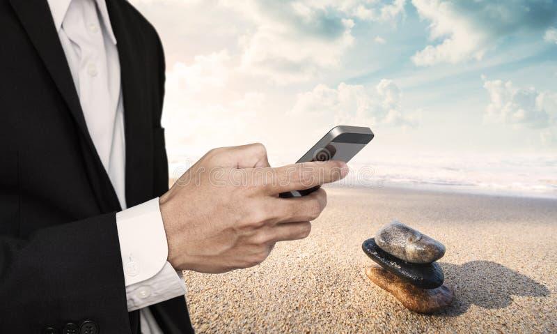 Homem de negócios que usa o telefone celular, com as pedras do equilíbrio na praia no fundo do nascer do sol foto de stock