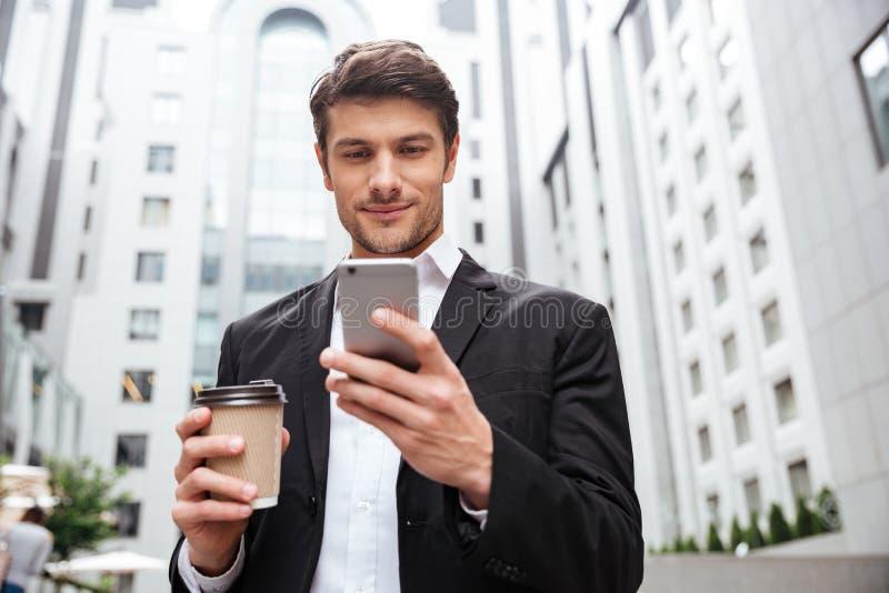 Homem de negócios que usa o telefone celular e bebendo o café na cidade fotografia de stock royalty free