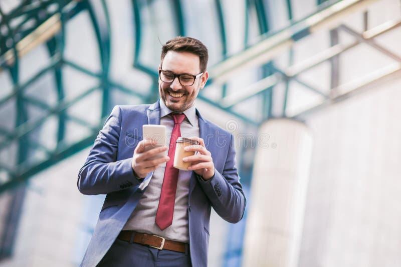 Homem de negócios que usa o telefone celular fora dos prédios de escritórios imagem de stock