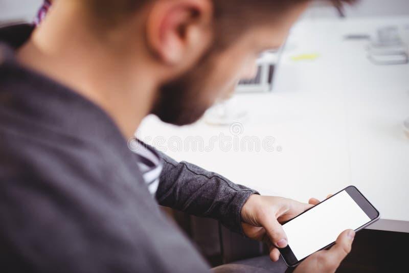 Homem de negócios que usa o telefone celular na reunião no escritório criativo imagens de stock royalty free