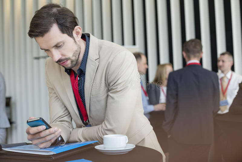 Homem de negócios que usa o telefone esperto quando ruptura de café no centro de convenções foto de stock royalty free