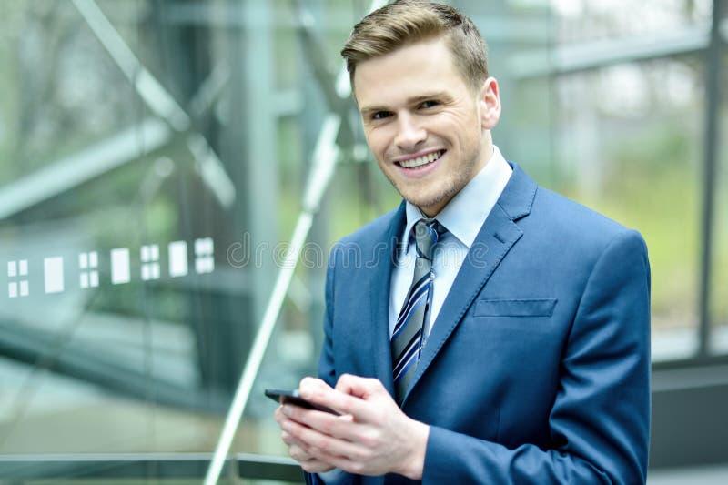 Homem de negócios que usa seu telefone celular imagens de stock