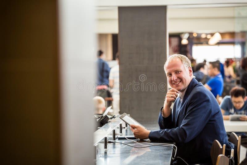 Homem de negócios que usa sua tabuleta no aeroporto imagens de stock royalty free