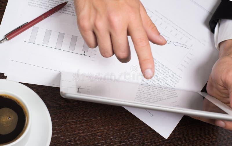 Homem de negócios que usa a tabuleta digital com cartas para planear e análise dos modelos comerciais, partida Engodo da finança  imagens de stock