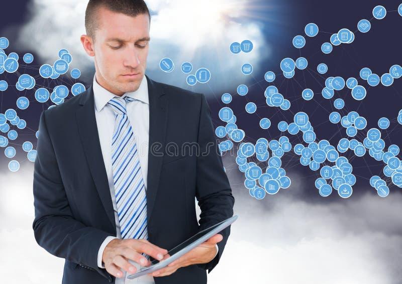 Homem de negócios que usa a tabuleta digital contra ícones da tecnologia no céu imagem de stock