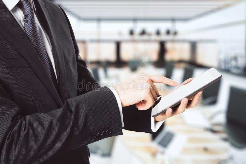 Homem de negócios que usa a tabuleta digital no fundo do espaço de escritórios imagens de stock