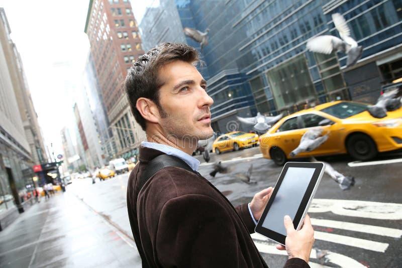 Homem de negócios que usa a tabuleta nas ruas de New York fotos de stock royalty free