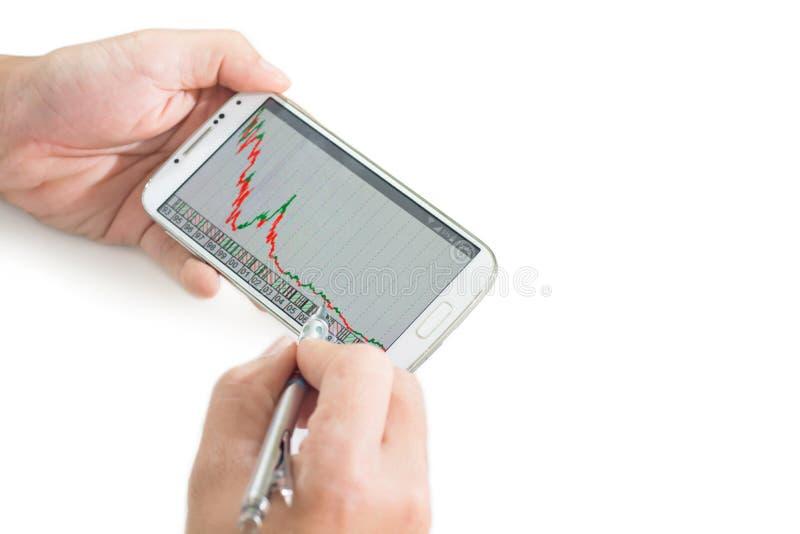 Homem de negócios que usa um dispositivo móvel para verificar estoques e dados do mercado foto de stock