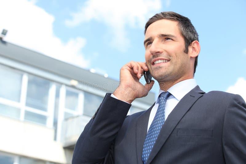 Homem de negócios que usa um telemóvel fotos de stock