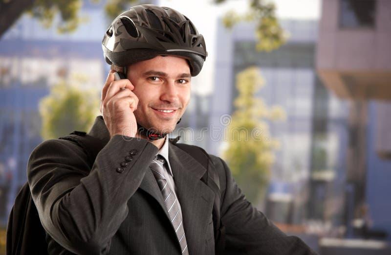 Homem de negócios que vai trabalhar pela bicicleta foto de stock royalty free