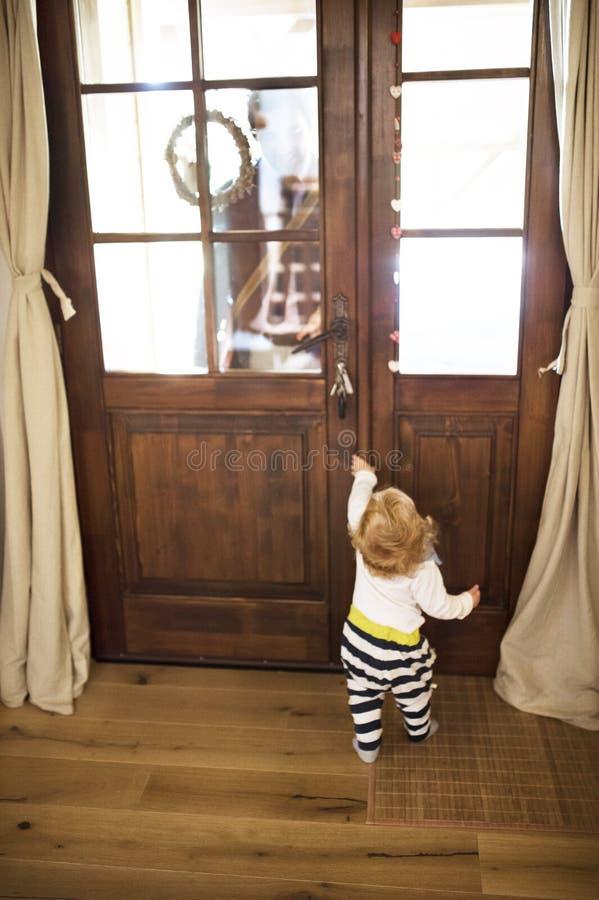Homem de negócios que vem em casa, filho pequeno na porta que dá boas-vindas a lhe fotos de stock