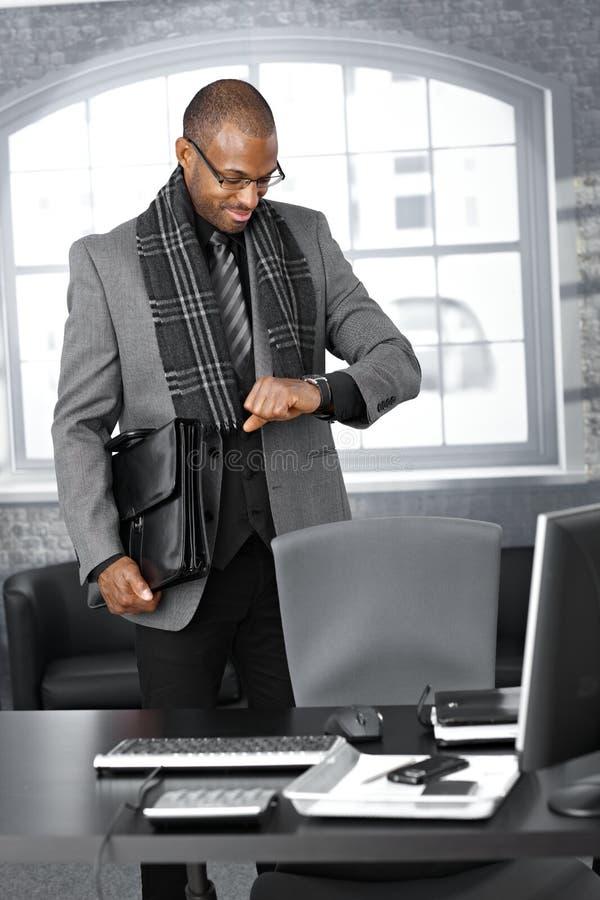 Homem de negócios que verific o tempo no escritório imagem de stock