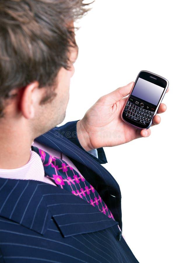 Homem de negócios que verific seu telefone para ver se há email. imagem de stock royalty free