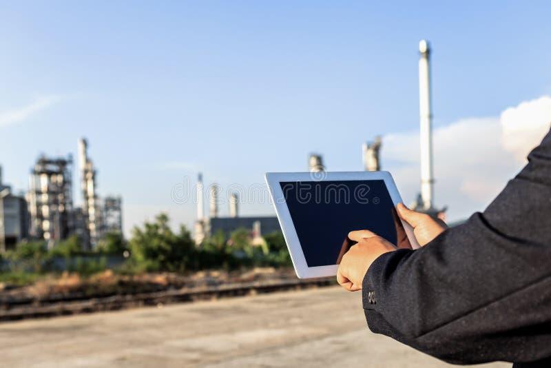 Homem de negócios que verifica em torno da planta de refinaria de petróleo com o céu claro foto de stock royalty free