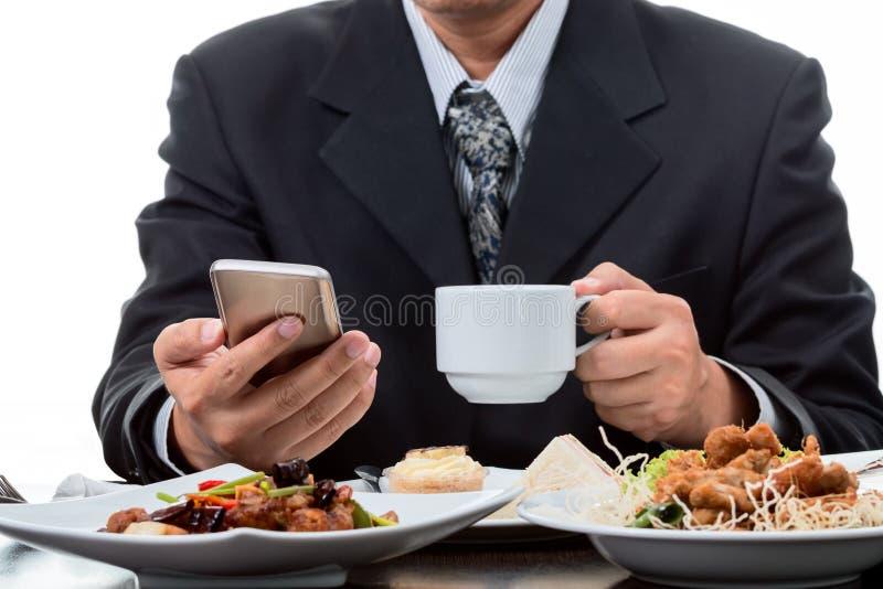 Homem de negócios que verifica a notícia do telefone celular e que toma o copo de café imagens de stock
