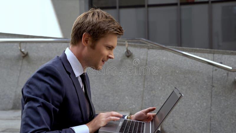 Homem de negócios que verifica o mercado de valores de ação usando o portátil no centro do escritório do ar livre das escadas imagem de stock royalty free