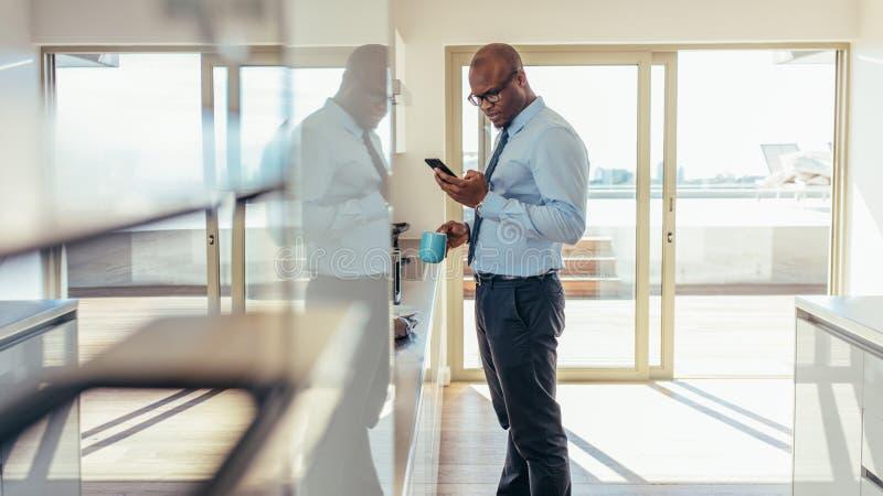 Homem de negócios que verifica o telefone celular ao comer o café da manhã imagens de stock royalty free