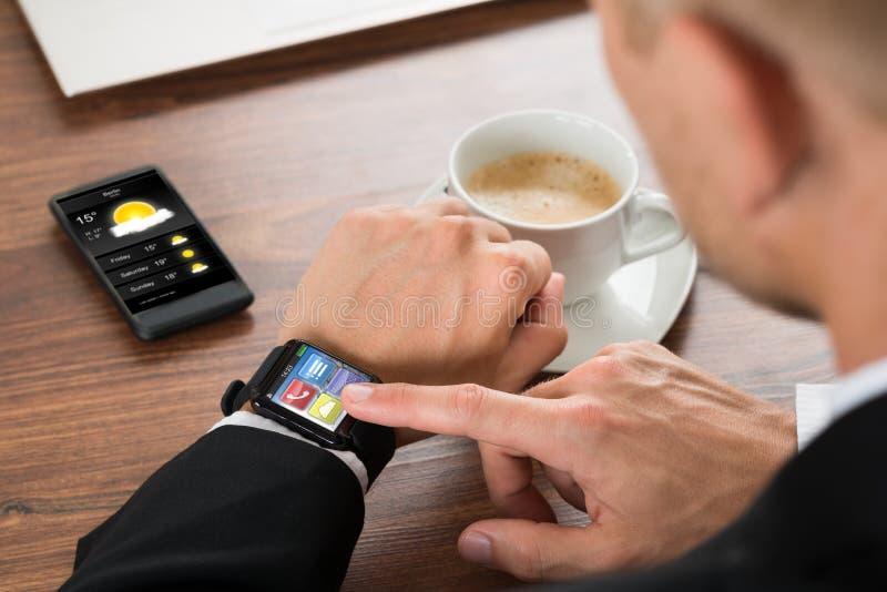 Homem de negócios que verifica o tempo no smartwatch imagem de stock