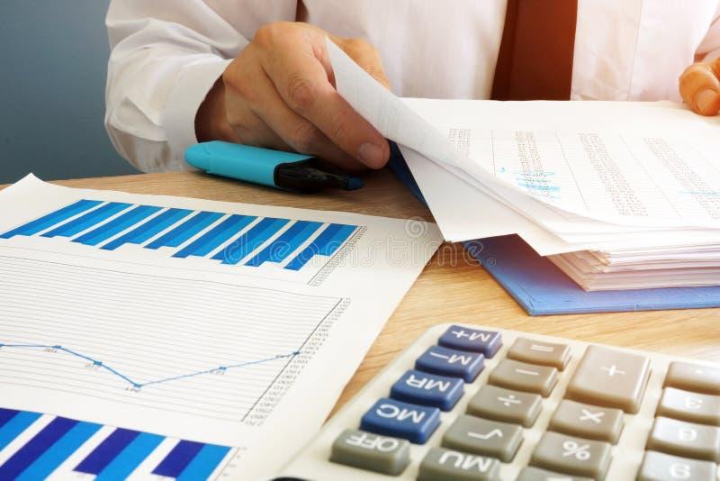 Homem de negócios que verifica originais financeiros Documento no escritório imagem de stock royalty free