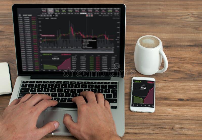 Homem de negócios que verifica seu mercado conservado em estoque em um portátil, da carta de comércio do gráfico dos estrangeiros fotografia de stock royalty free