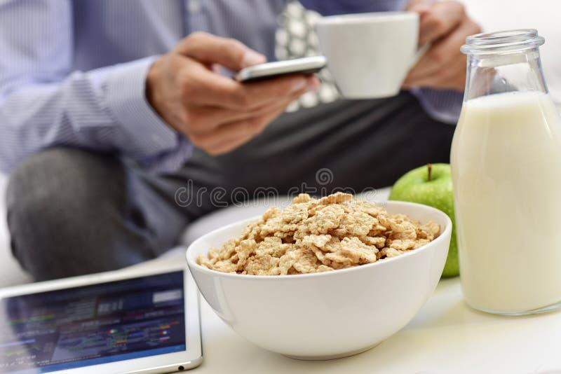 Homem de negócios que verifica seu smartphone durante o tempo de café da manhã foto de stock royalty free