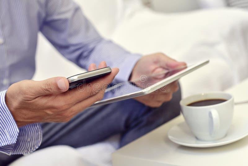 Homem de negócios que verifica seu smartphone e sua tabuleta fotos de stock