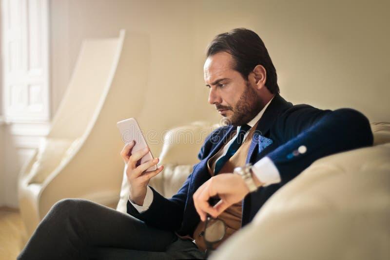 Homem de negócios que verifica seu telefone fotos de stock royalty free