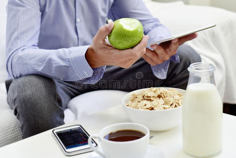 Homem de negócios que verifica sua tabuleta durante o café da manhã fotografia de stock royalty free