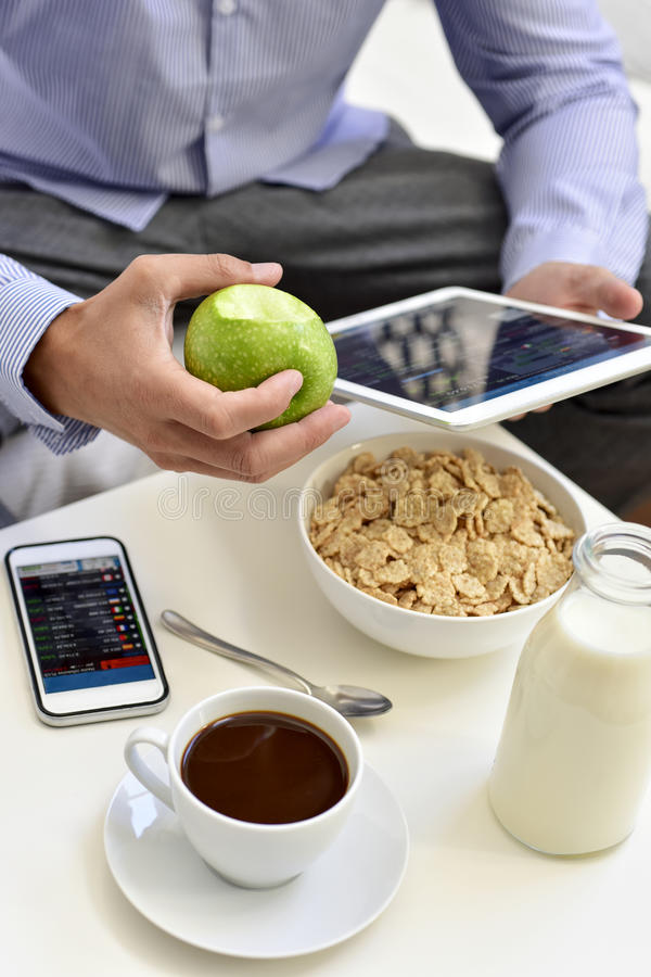 Homem de negócios que verifica sua tabuleta durante o tempo de café da manhã fotografia de stock