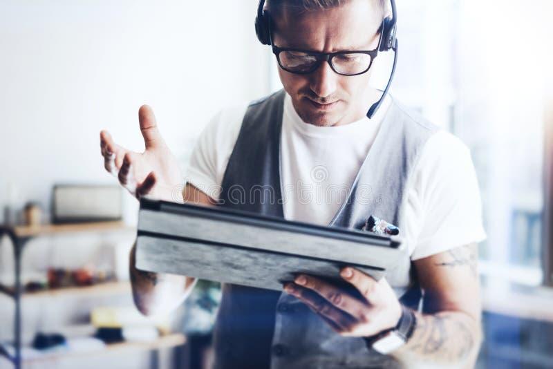 Homem de negócios que veste auriculares audio e que faz a conversação video através da tabuleta digital Homem elegante que trabal fotografia de stock