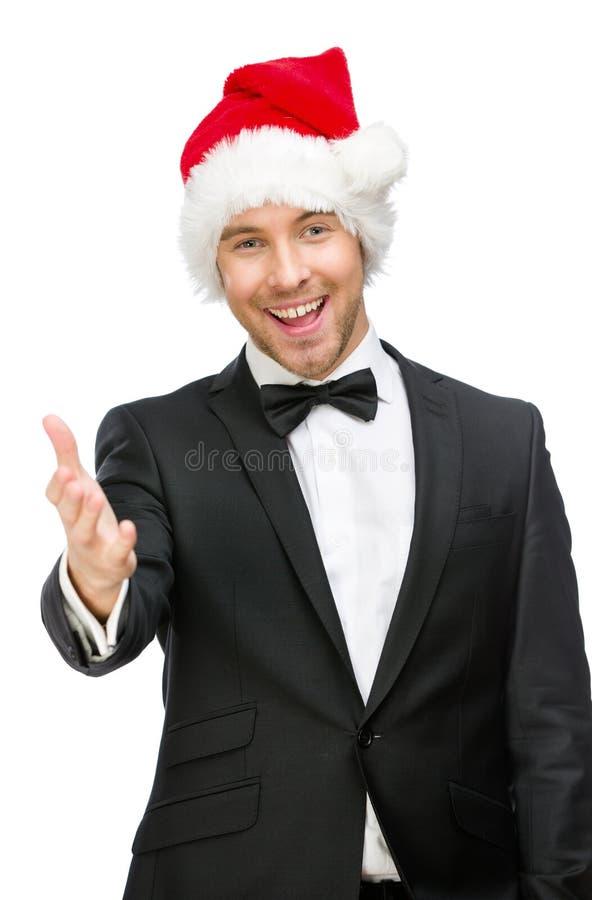 Homem de negócios que veste gestos do aperto de mão do tampão de Santa Claus fotografia de stock