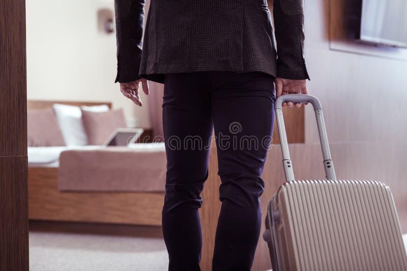 Homem de negócios que veste o revestimento escuro que toma sua bagagem na sala de hotel fotos de stock