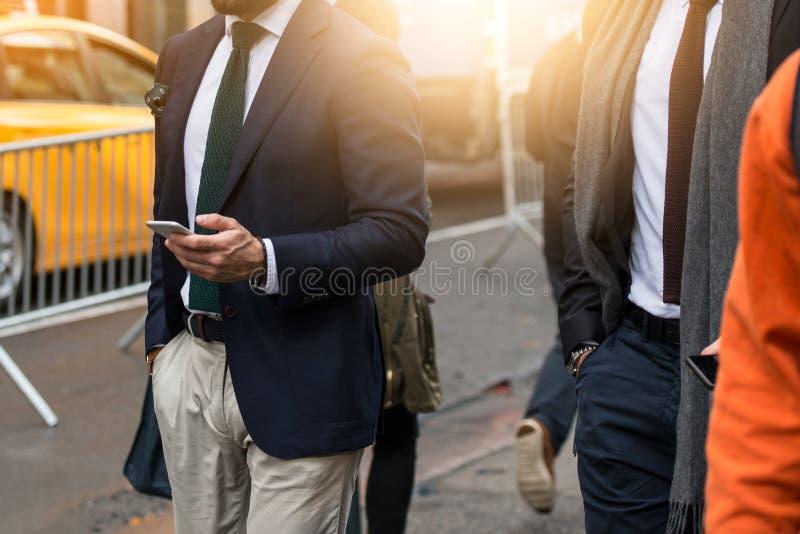 Homem de negócios que veste o terno preto e que usa o smartphone moderno durante a caminhada ao escritório na rua da cidade fotografia de stock